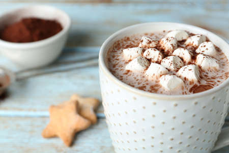 Delicious hot cocoa drink with marshmallows in cup on light blue wooden table, closeup