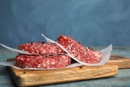 Raw meat cutlets for burger on blue wooden table. Space for text Stock fotó