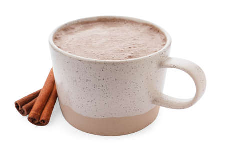 Delicious cocoa drink in cup and cinnamon sticks on white background