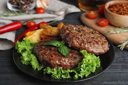 Grilled meat cutlets for burger on black wooden table