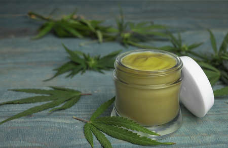 Jar of hemp cream on blue wooden table, space for text. Organic cosmetics