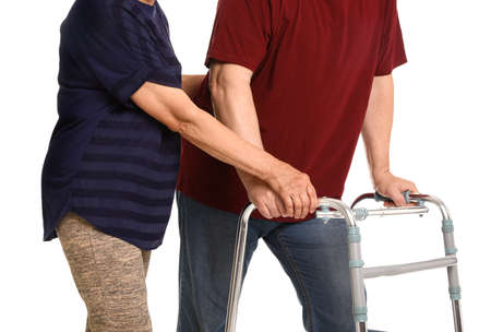 Elderly woman helping her husband with walking frame on white background, closeup Stock fotó