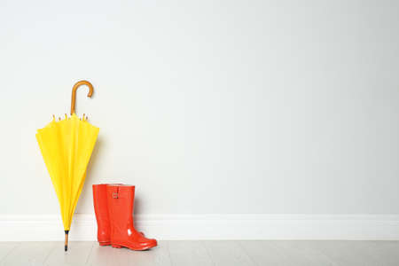 Colorful umbrella and rubber boots on floor against white wall. Space for text 写真素材