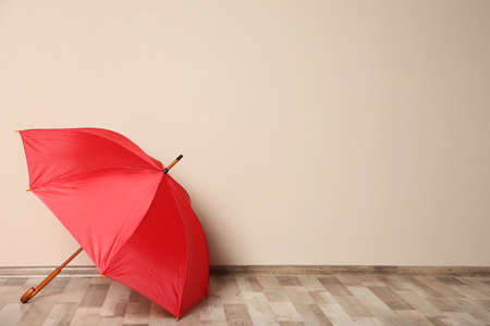 Colorful umbrella on floor against beige wall. Space for text Stock Photo