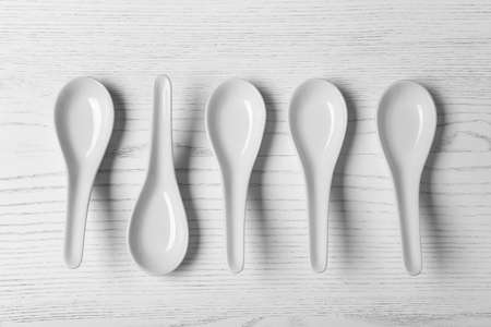 Flat lay composition with miso soup spoons on white wooden table