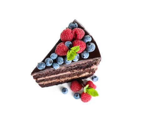 Piece of delicious chocolate cake decorated with fresh berries on white background, above view