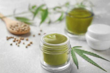 Jars of hemp cream and seeds on grey table. Organic cosmetics