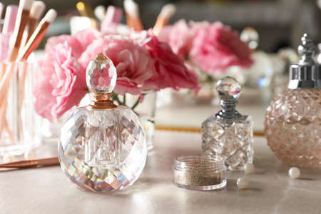 Different elegant perfume bottles on dressing table Foto de archivo