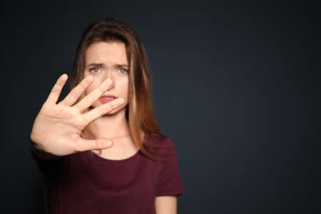 Young woman making stop gesture against dark background, focus on hand. Space for text