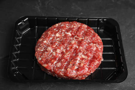 Plastic container with raw meat cutlet for burger on black table