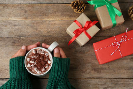 Woman holding cup of delicious cocoa drink at wooden table with Christmas presents, top view Stock fotó