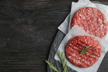 Raw meat cutlets for burger on black wooden table, top view. Space for text