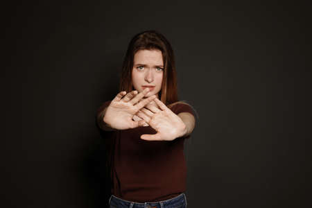 Young woman making stop gesture against dark background