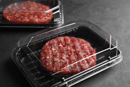 Plastic containers with raw meat cutlets for burger on grey table