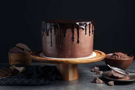 Freshly made delicious chocolate cake on grey table against black background