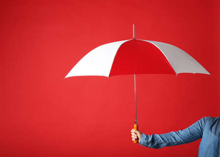 Woman holding modern colorful umbrella on red background, closeup. Space for text