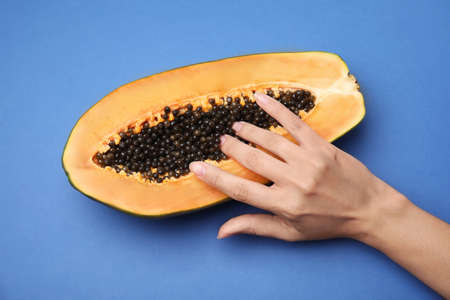 Young woman touching half of papaya on blue background, top view. Sex concept
