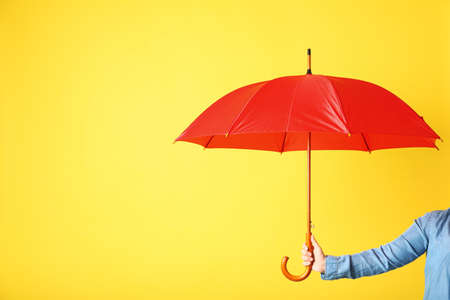 Woman holding modern colorful umbrella on yellow background, closeup. Space for text