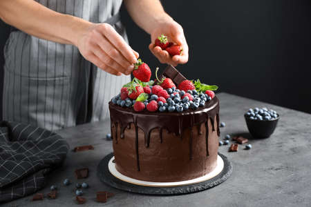 Woman decorating delicious chocolate cake with fresh strawberries at table, closeup Stock fotó