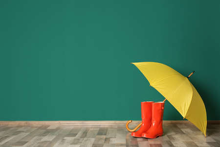 Colorful umbrella and rubber boots on floor against green wall. Space for text