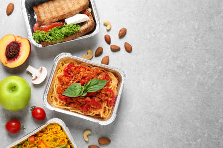 Lunchboxes on light grey table, flat lay. Healthy food delivery