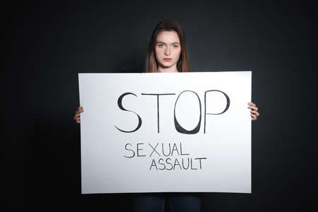 Young woman holding card with words STOP SEXUAL ASSAULT against dark background