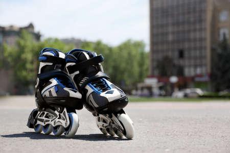 Modern inline roller skates in city park on sunny day