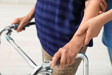 Caretaker helping elderly woman with walking frame on light background, closeup