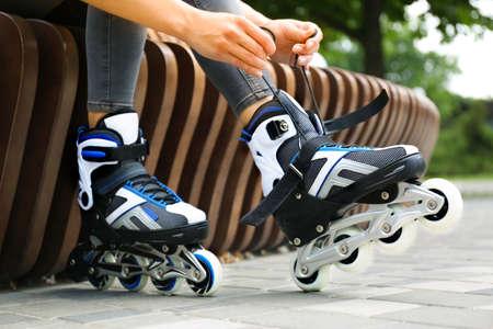 Woman wearing modern inline roller skates in city park, closeup