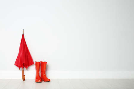 Colorful umbrella and rubber boots on floor against white wall. Space for text Stock Photo