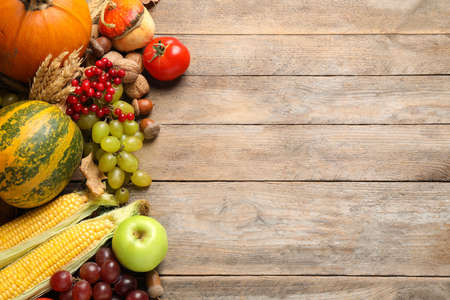 Flat lay composition with autumn vegetables and fruits on wooden background, space for text. Happy Thanksgiving day