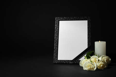 Funeral photo frame with ribbon, white roses and candle on dark table against black background. Space for design Banque d'images - 132239231