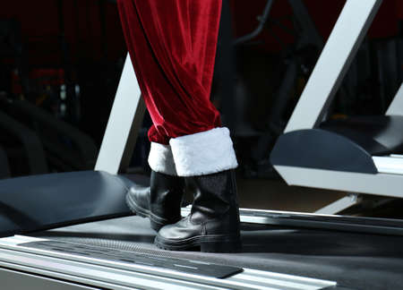 Authentic Santa Claus training on treadmill in modern gym