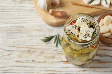 Composition with pickled feta cheese in jar on white wooden table, space for text