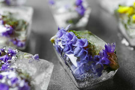 Ice cubes with flowers on grey stone table, closeup Stock Photo