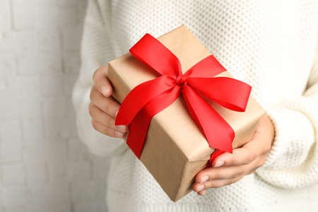 Young woman holding Christmas gift on light background, closeup