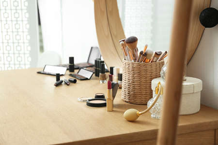 Cosmetics and brushes on dressing table in makeup room