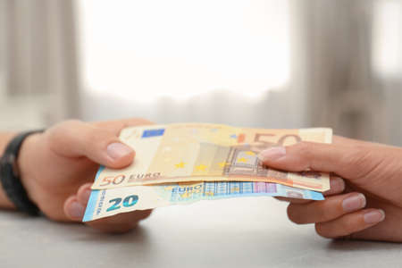 People with Euro banknotes at table indoors, closeup