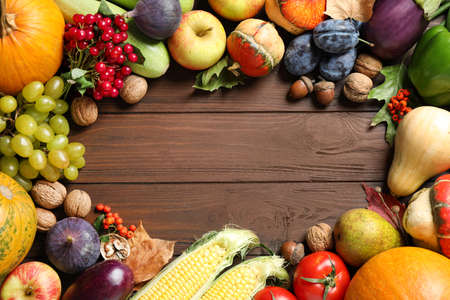 Frame made of autumn vegetables and fruits on wooden background, top view with space for text. Happy Thanksgiving day