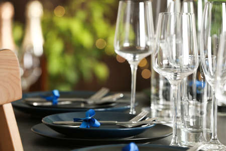 Table setting with empty glasses, plates and cutlery indoors. Space for text