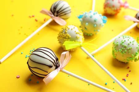 Different tasty cake pops with sprinkles on yellow background Reklamní fotografie