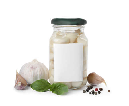 Composition with jar of pickled garlic on white background