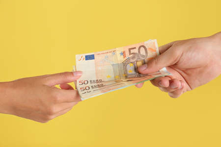 People with Euro banknotes on yellow background, closeup