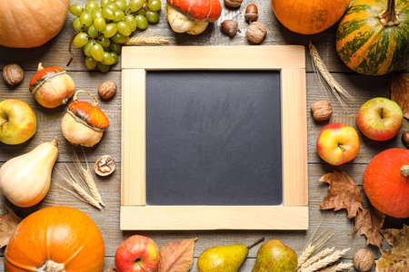 Chalkboard with space for text, autumn fruits and vegetables on wooden background, flat lay. Happy Thanksgiving day Stockfoto