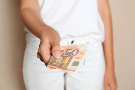 Woman with Euro banknotes on brown background, closeup Stok Fotoğraf