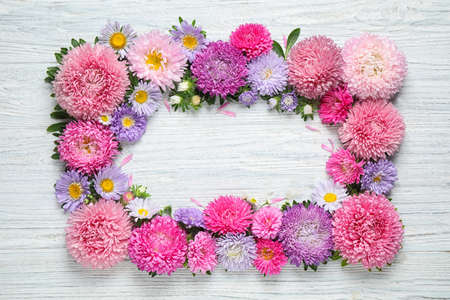 Frame made of beautiful aster flowers on white wooden table. Space for text