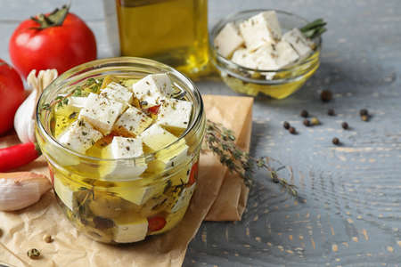 Composition with pickled feta cheese in jar on grey wooden table, space for text