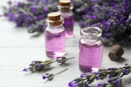 Bottles with essential oil and lavender flowers on white wooden table