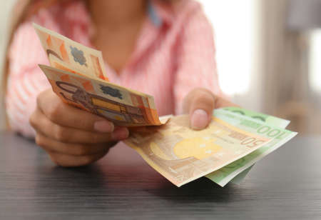 Woman with Euro banknotes at table indoors, closeup