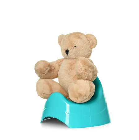 Teddy bear sitting on blue potty against white background. Toilet training Фото со стока